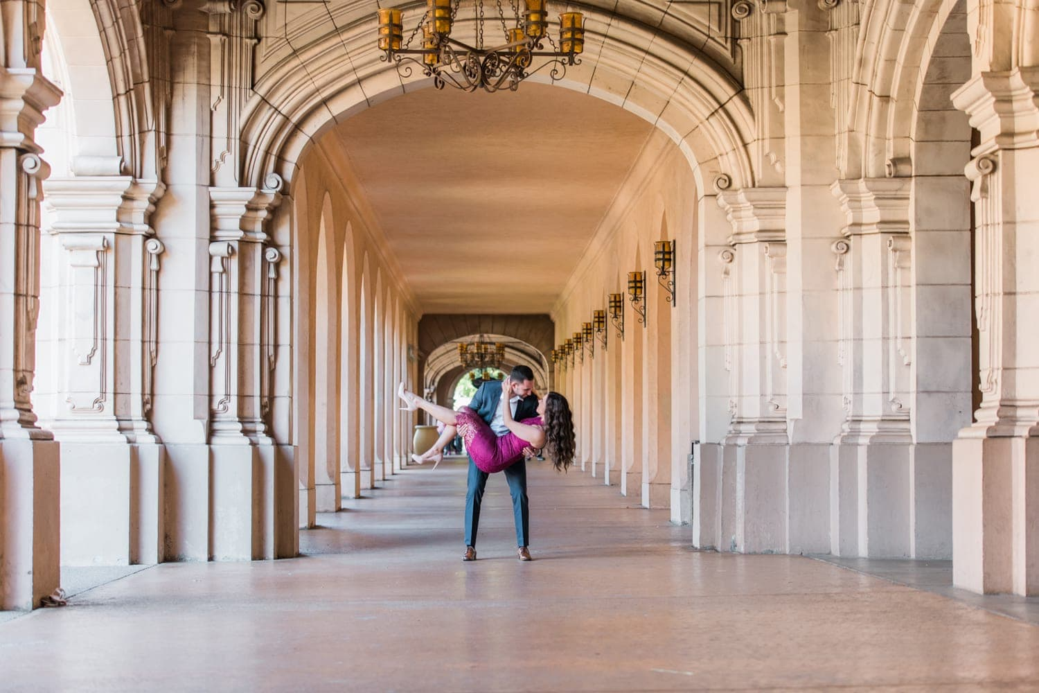 Couple holding each other under the archway at Balboa Park in San Diego, California.