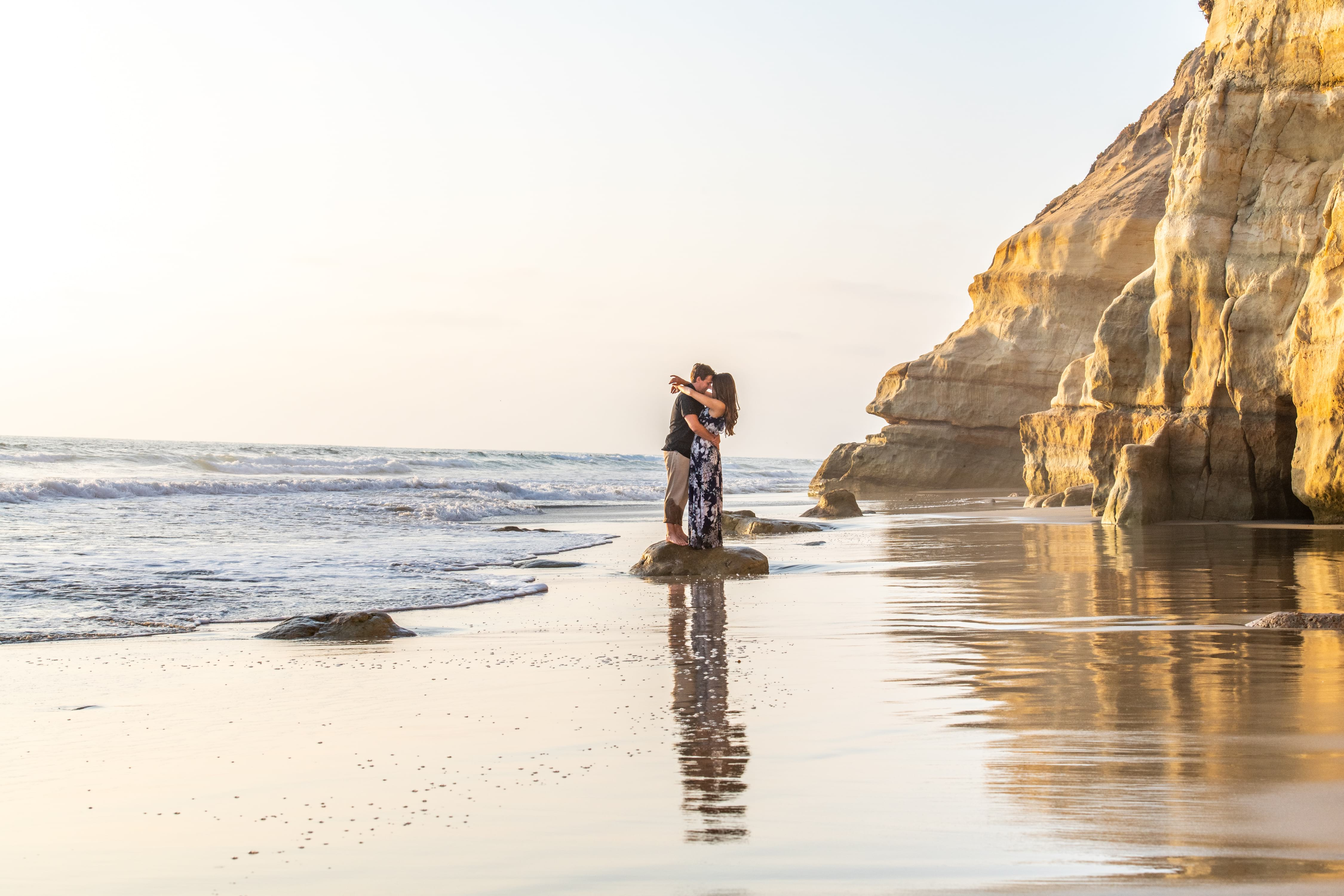 Couple kissing at Del Mar Dog Beach.