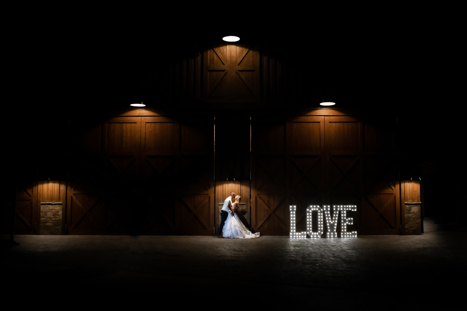 Bride and groom at night in front of a barn.