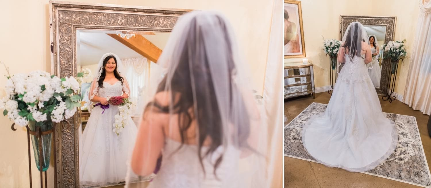 Bride looking in big mirror after putting on her wedding dress.
