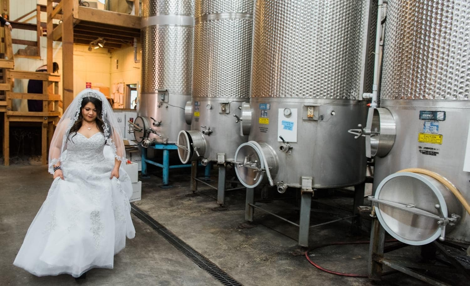 Bride walking by Wine Barrels at the winery on the way to her ceremony.