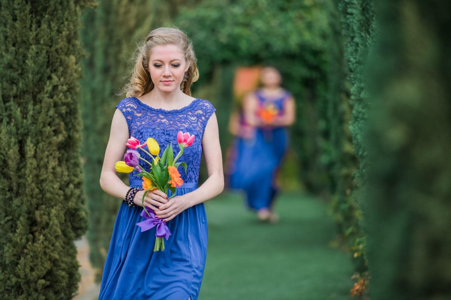 Bridesmaid walking to the ceremony with her bouquet.