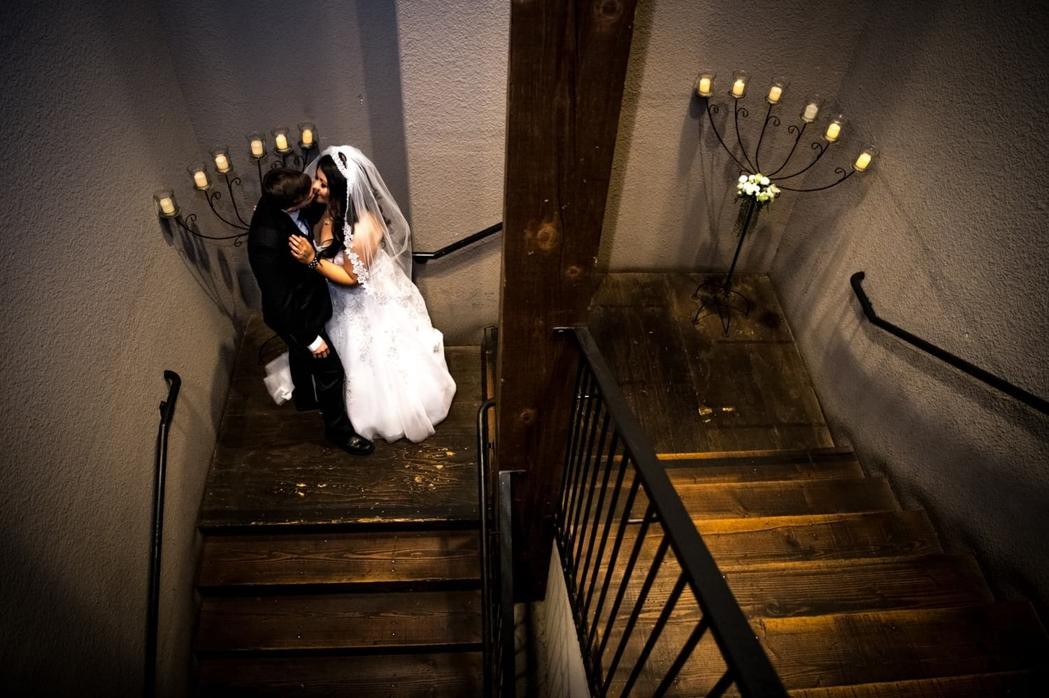 Bride and groom kissing on a staircase.