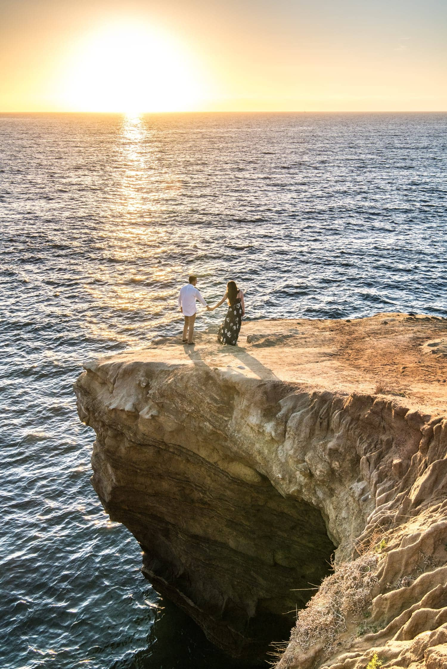 Couple holding hands on a cliff at Sunset Cliffs.