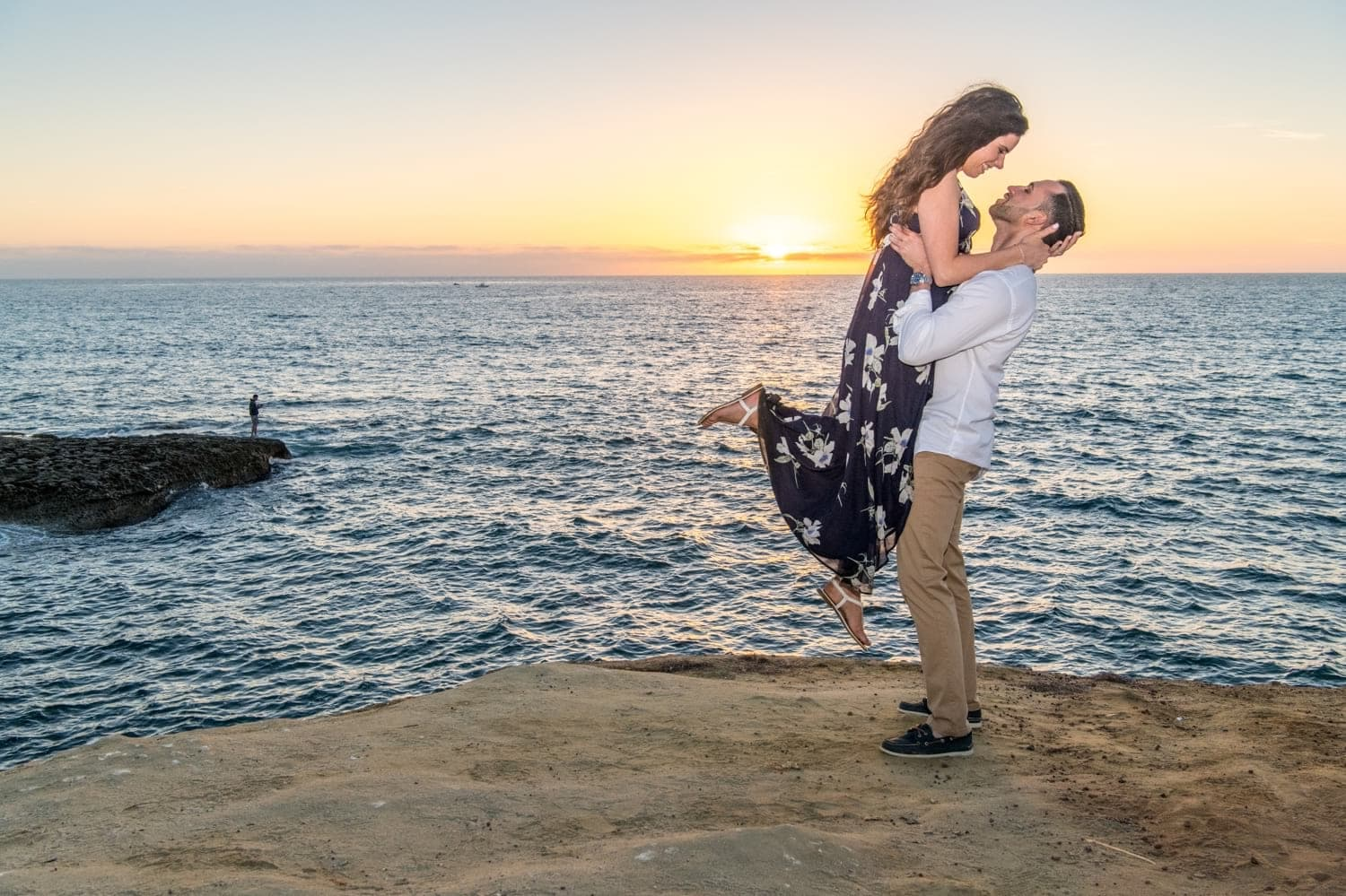 Guy lifting up his bride to be for a photo at sunset.