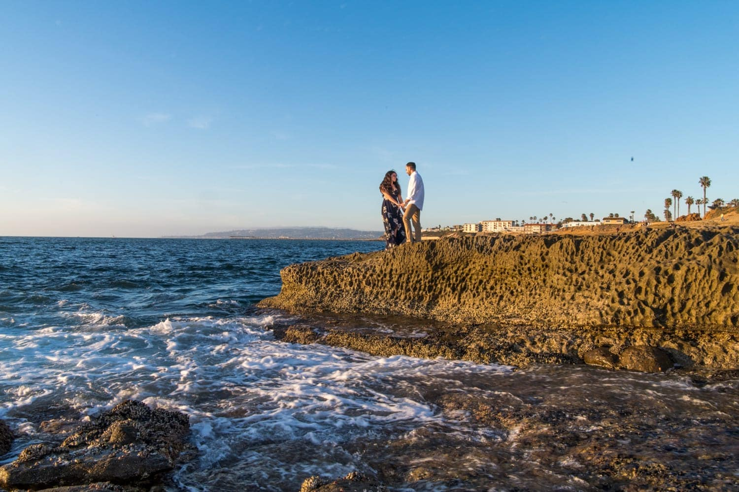Couple standing on rocks by the waters edge in San Diego.