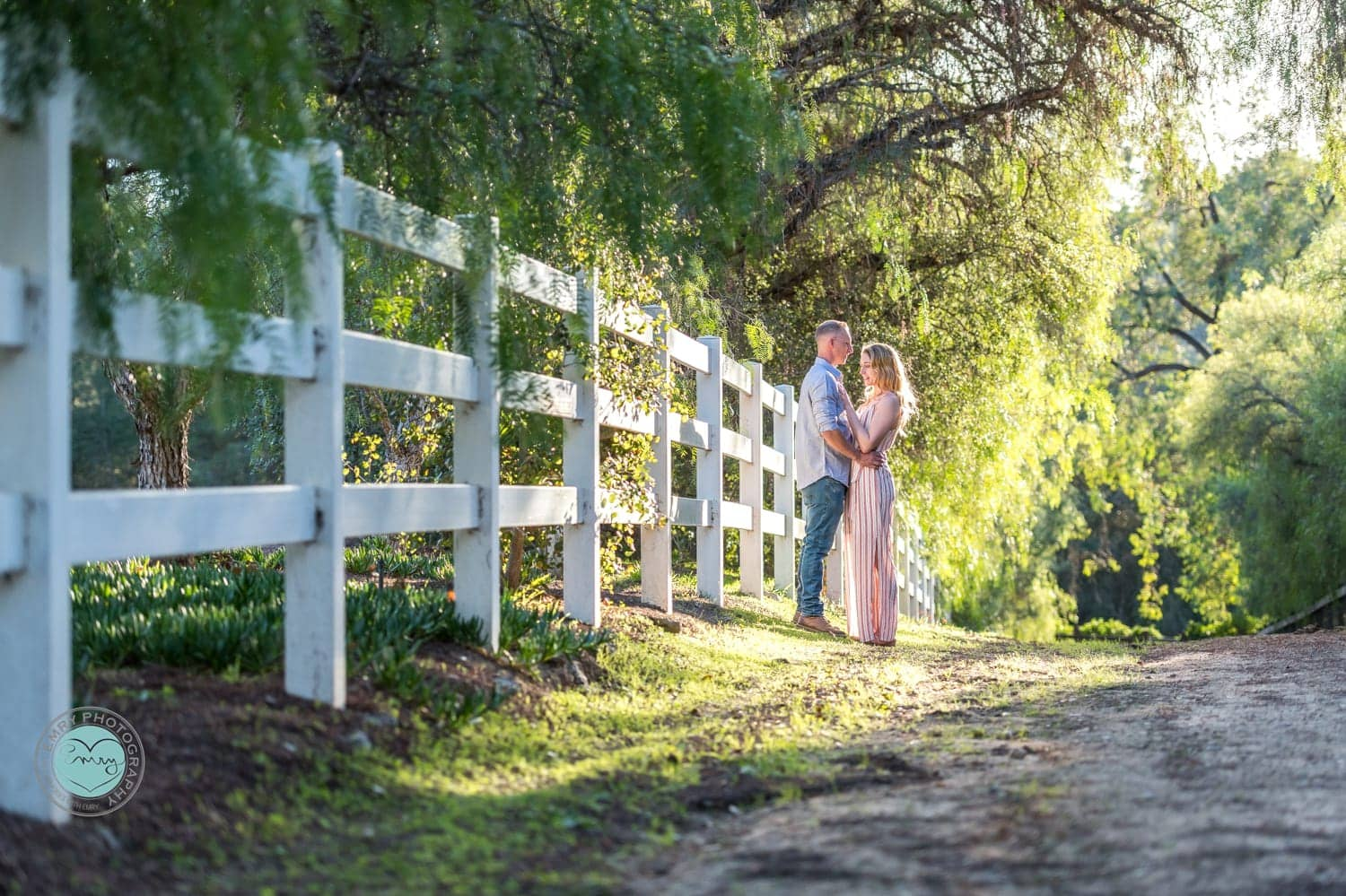 Engagement session on a dirt road with a white fence.