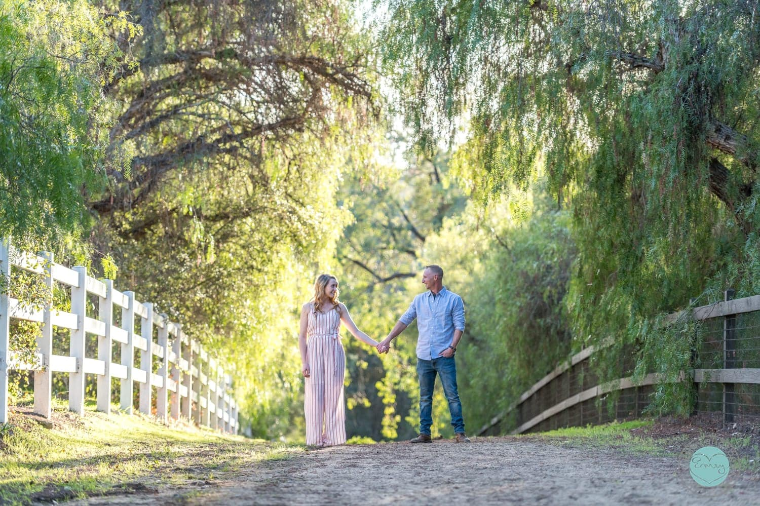 Couple standing in the middle of a dirt road holding hands.