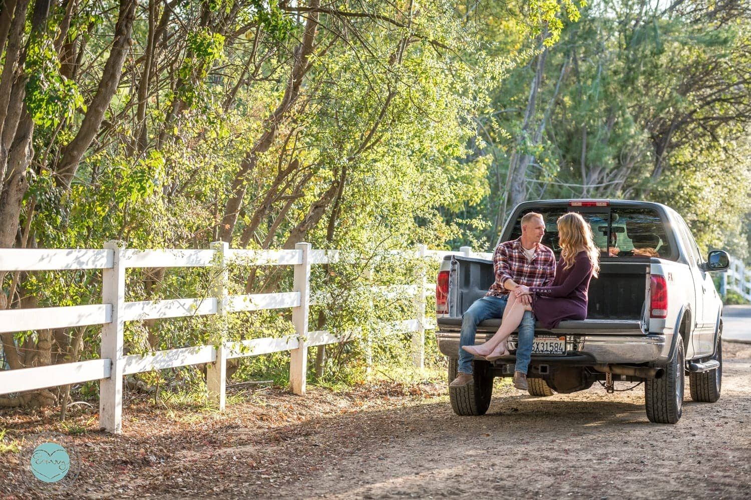 Couple sitting in the bed of a truck for their engagement photos.