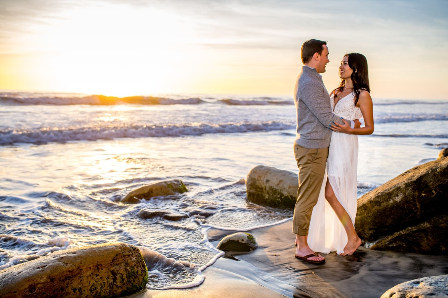 Bride and groom standing on the beach at sunset.