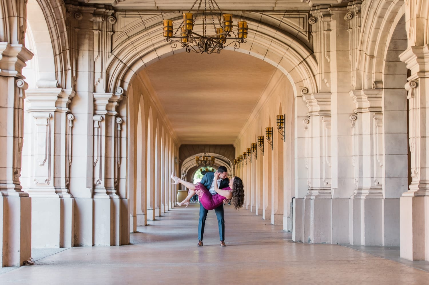 Groom lifting his bride and dipping her at Balboa Park.