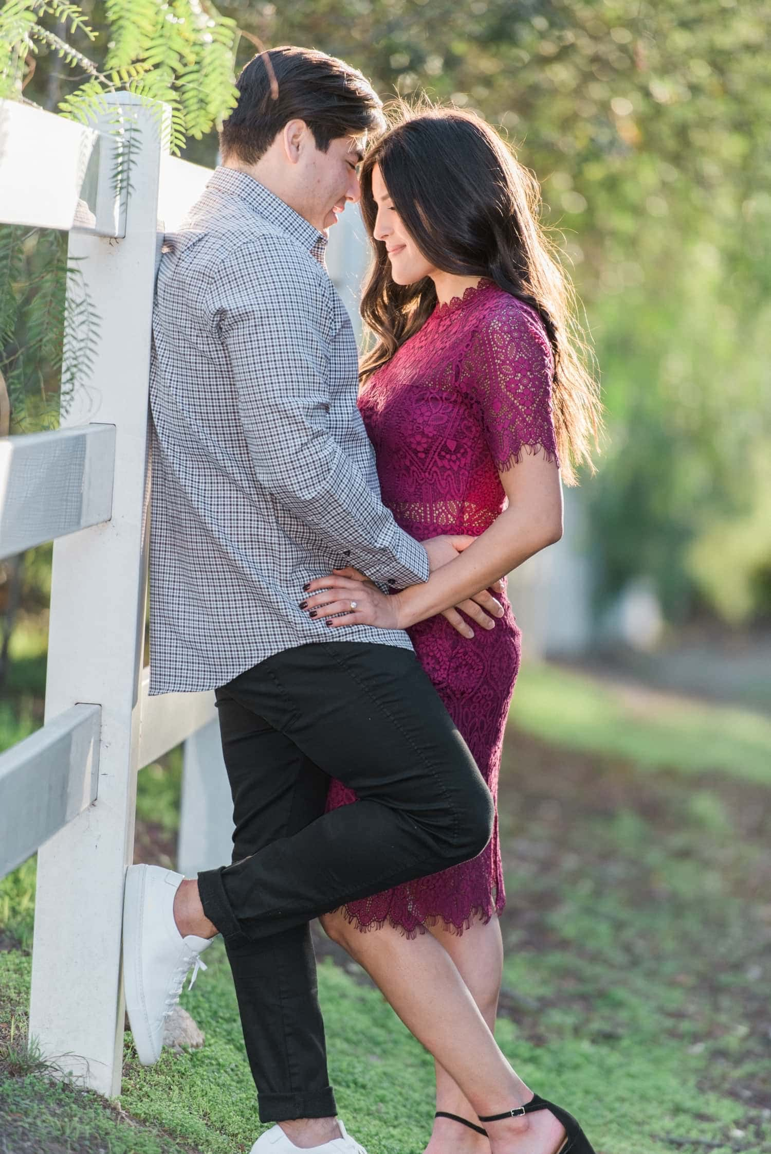 Couple leaning against a white fence.
