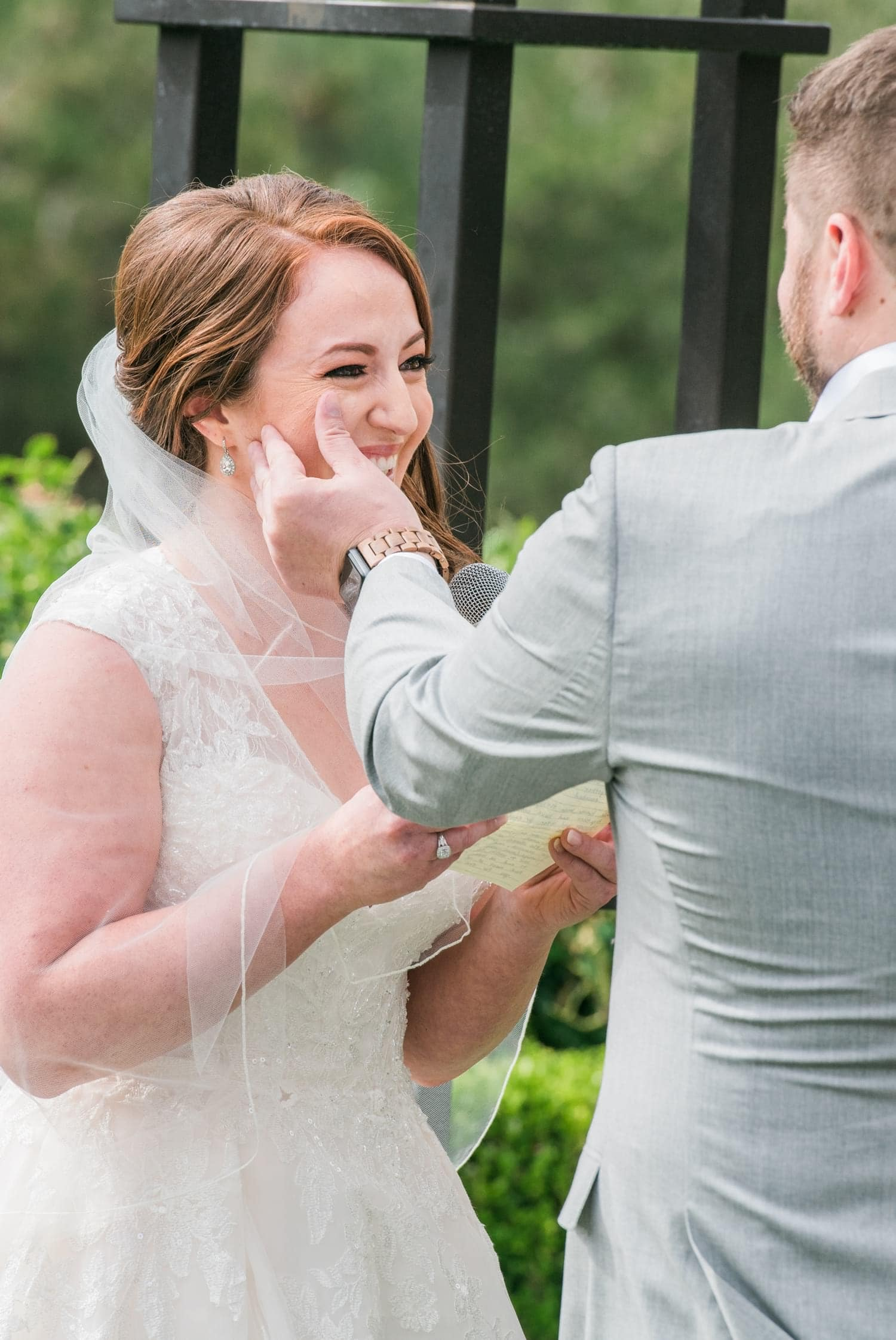 Groom wiping away tears from his bride's face.