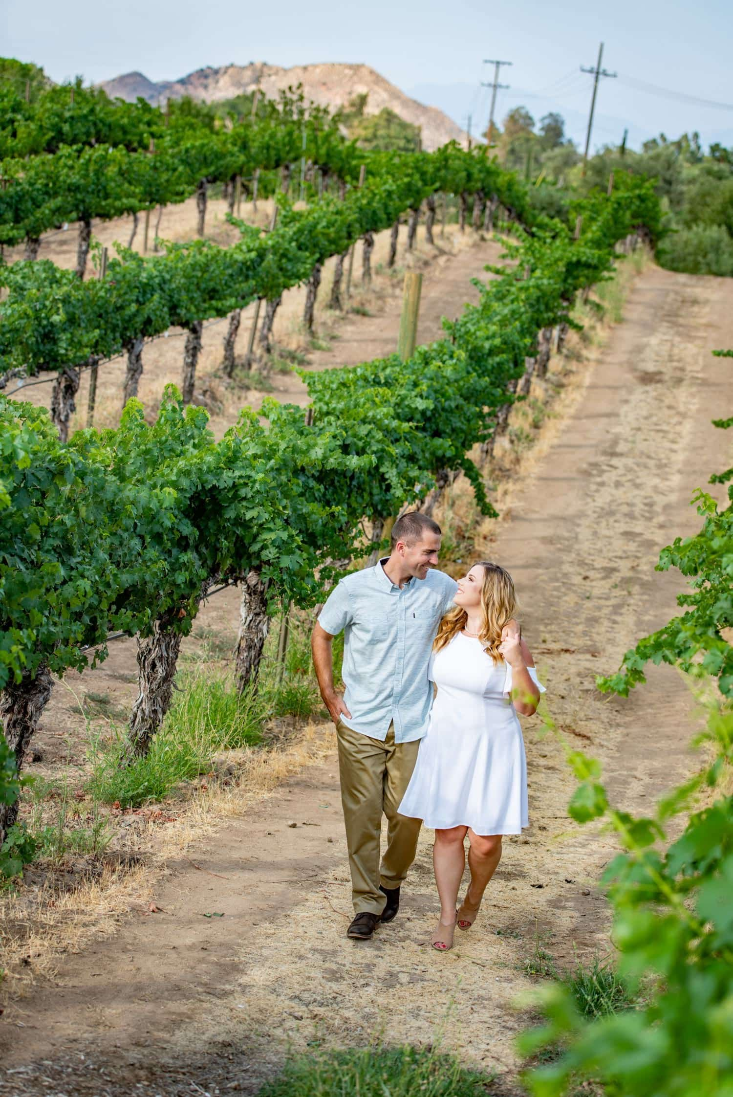 Couple walking through the vines for their engagement session at Wilson Creek Winery in Temecula.