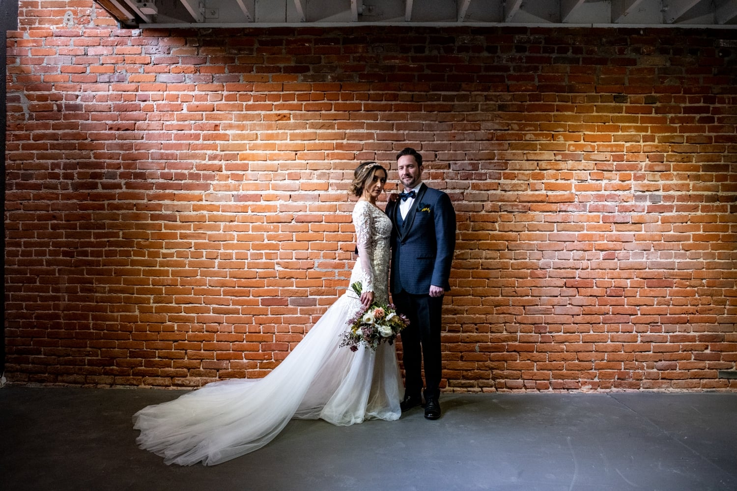 Bride and groom against a brick wall in the basement of the Pannikin Building.
