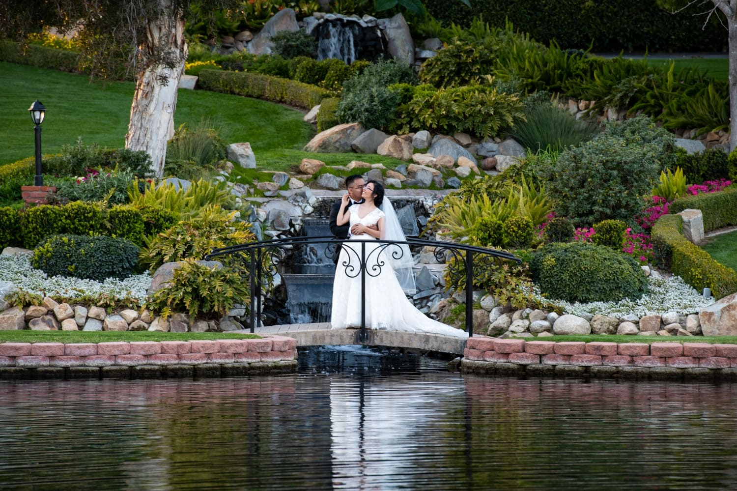 Bride and groom by the pond at the Grand Tradition Estate in Fallbrook, CA.