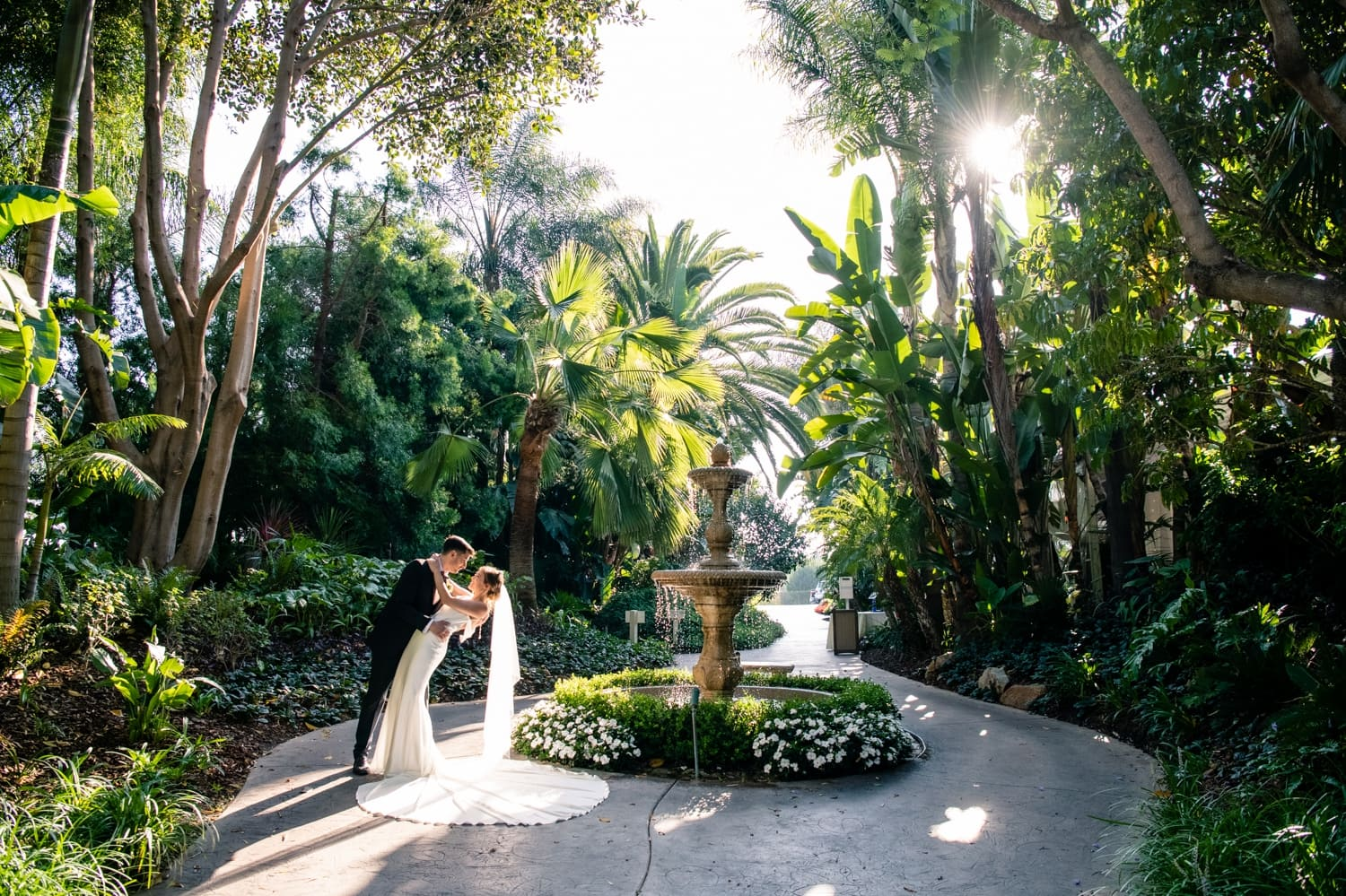 Bride and groom by the fountain in Arbor Terrace at Grand Tradition Estate in Fallbrook, CA.