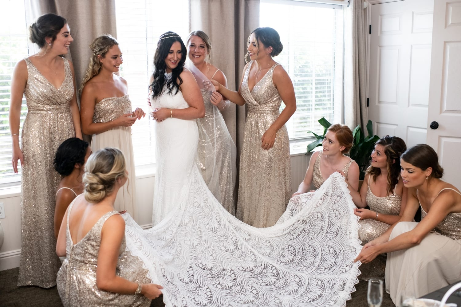 Bridesmaids helping bride get ready for her wedding.