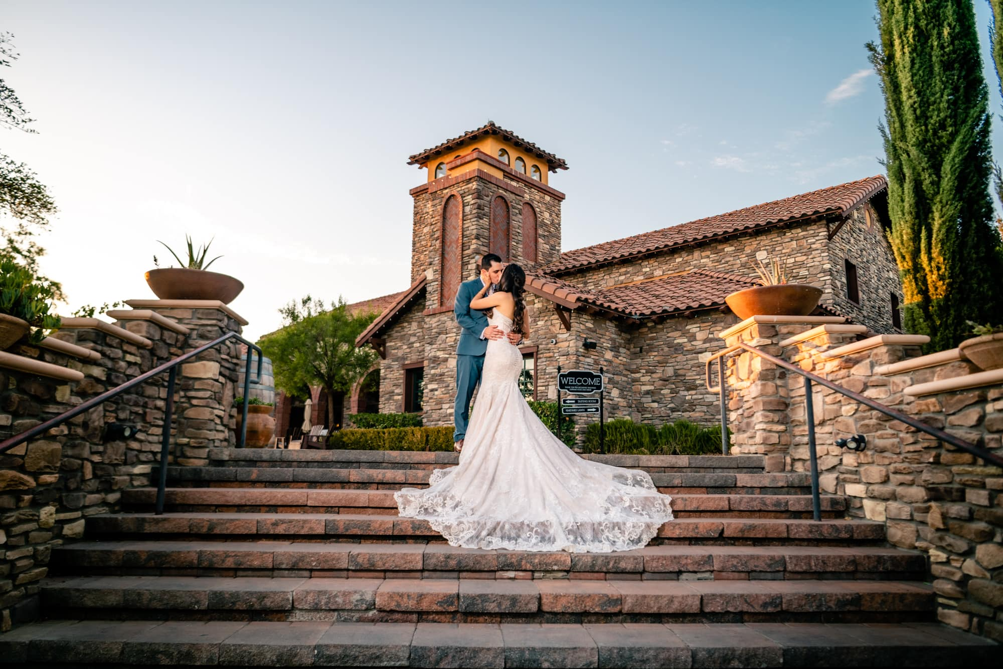 Bride and groom kissing on the front steps of Lorimar Winery in Temecula, CA.