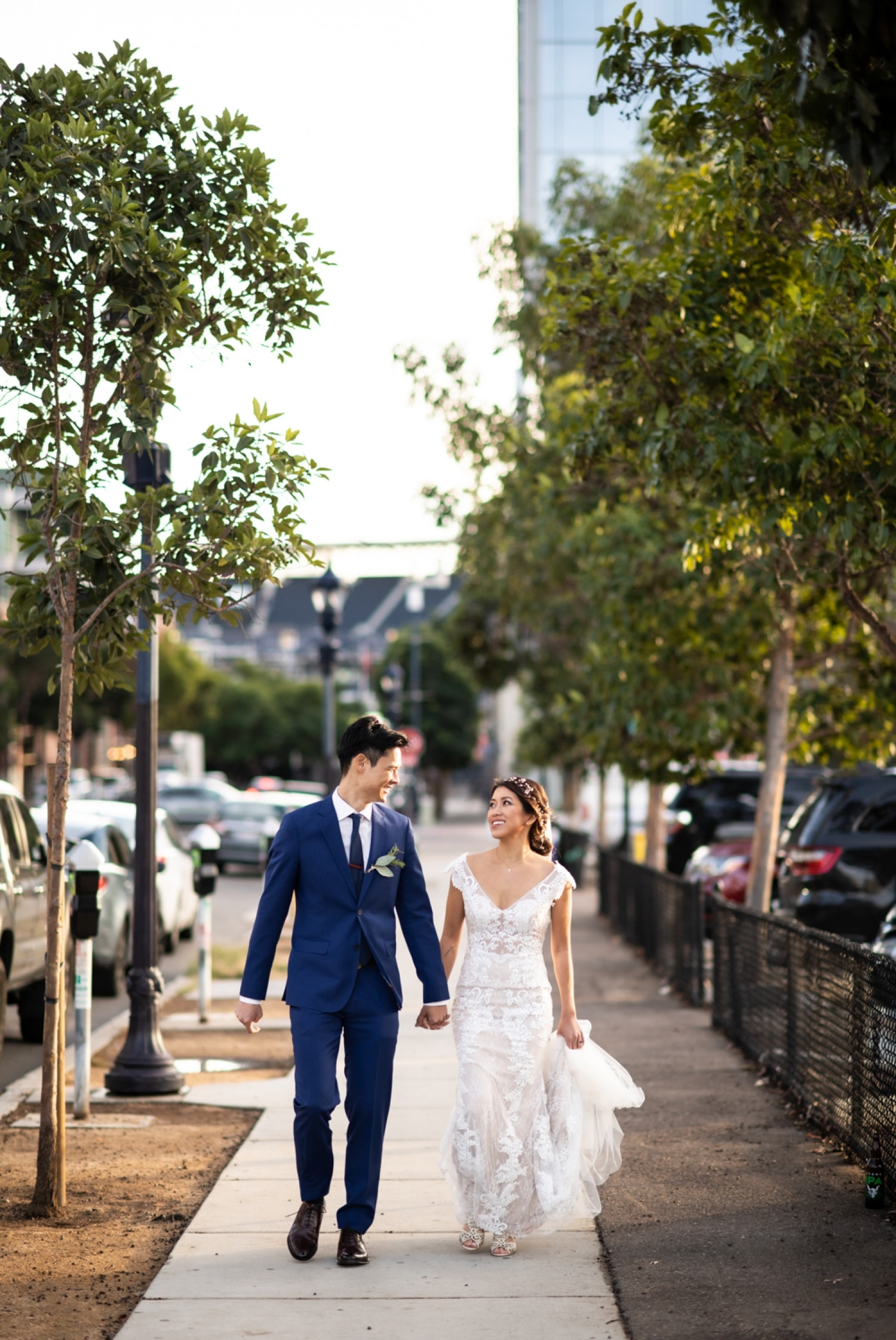 Bride and groom walking down the street in downtown San Diego.