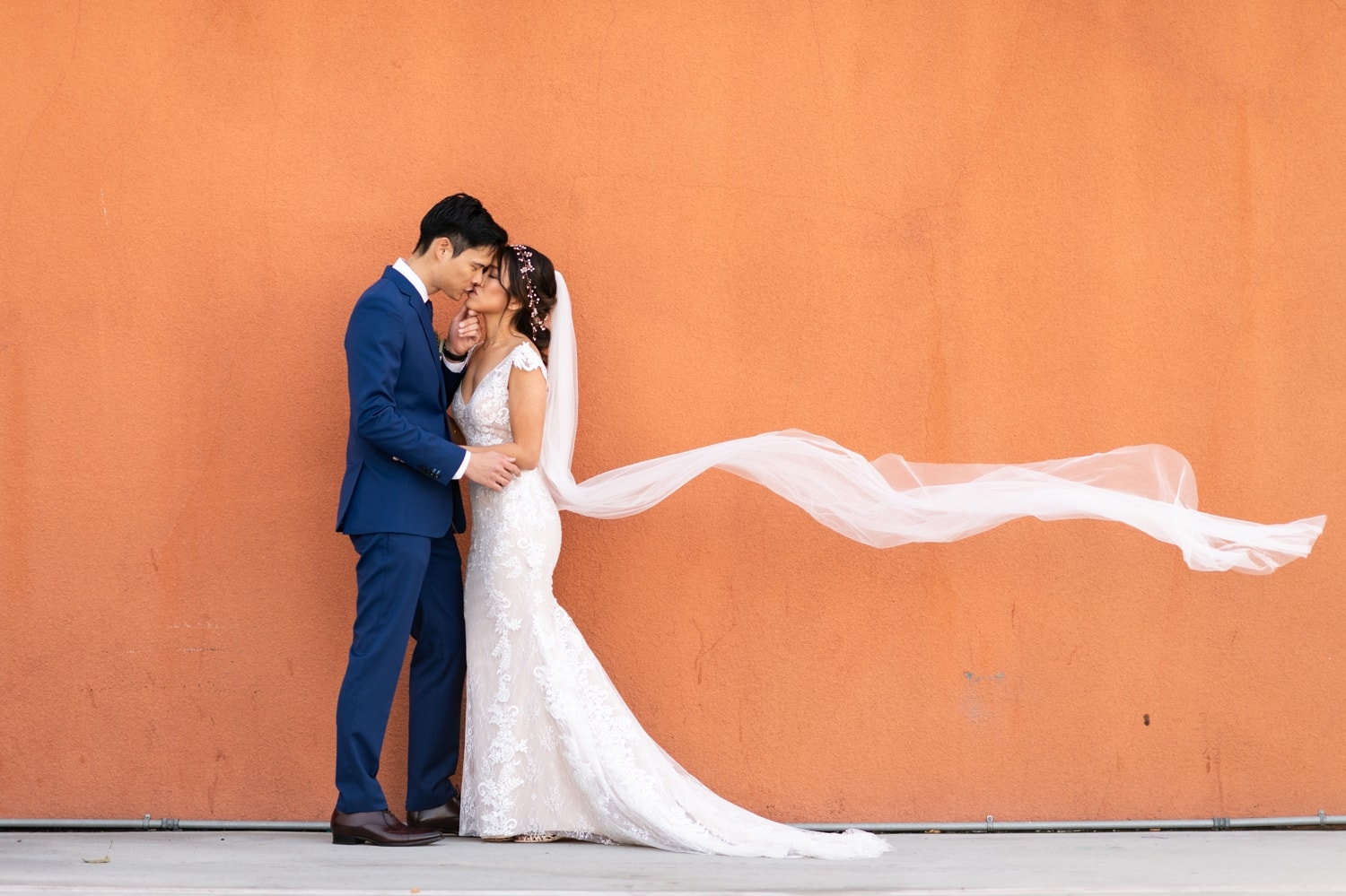 Bride and groom kissing in front of an orange wall in San Diego.