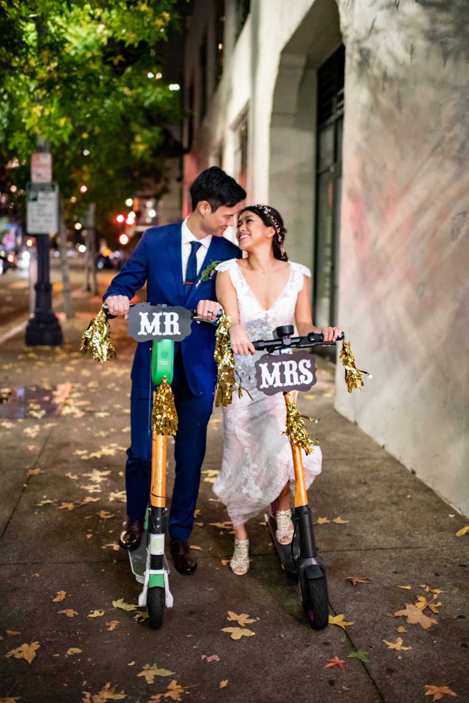 Bride and groom on decorated byrd scooters in San Diego.