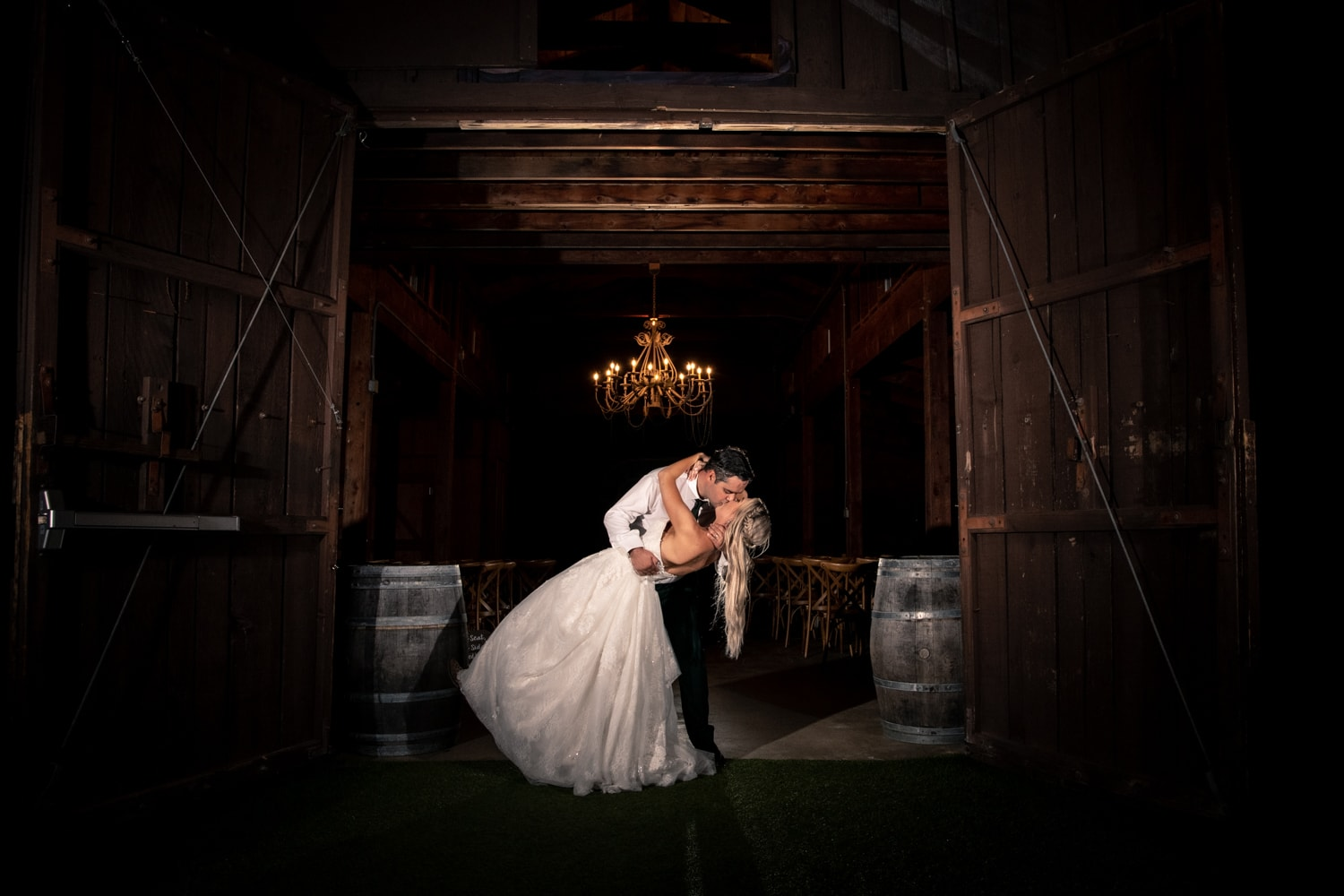 Bride and groom kissing at the barn at Ethereal Gardens in Escondido, CA.
