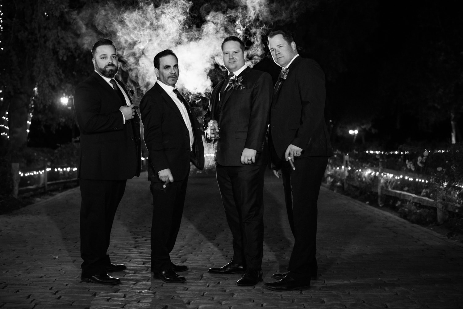 Groom and groomsmen smoking cigars at a San Diego wedding.
