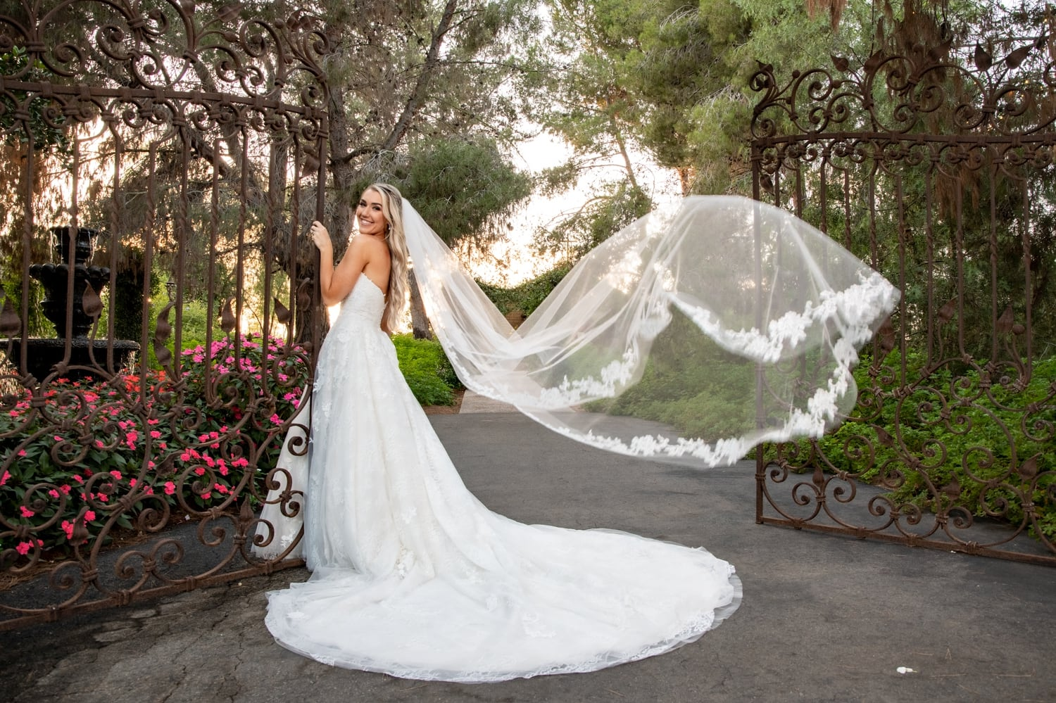 Bride with her veil flowing in the air at the gate at Ethereal Gardens.