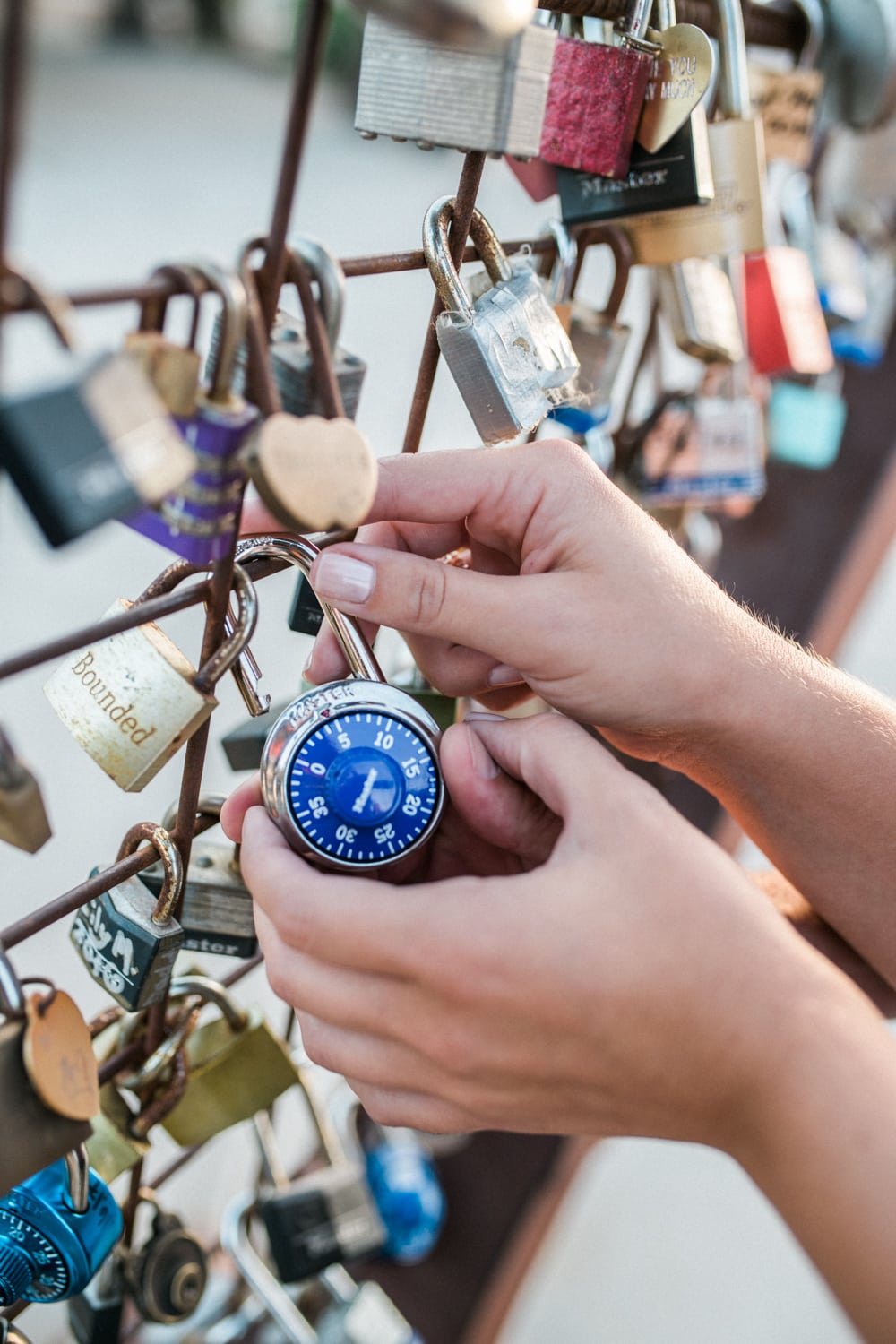Couple attaching love lock to the heart sculpture in downtown Vista, California.