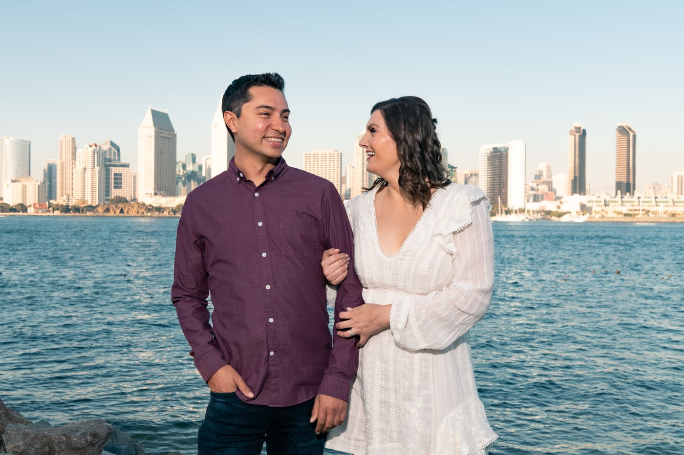 Engaged couple cuddling in front of San Diego skyline at Centennial Park in San Diego.