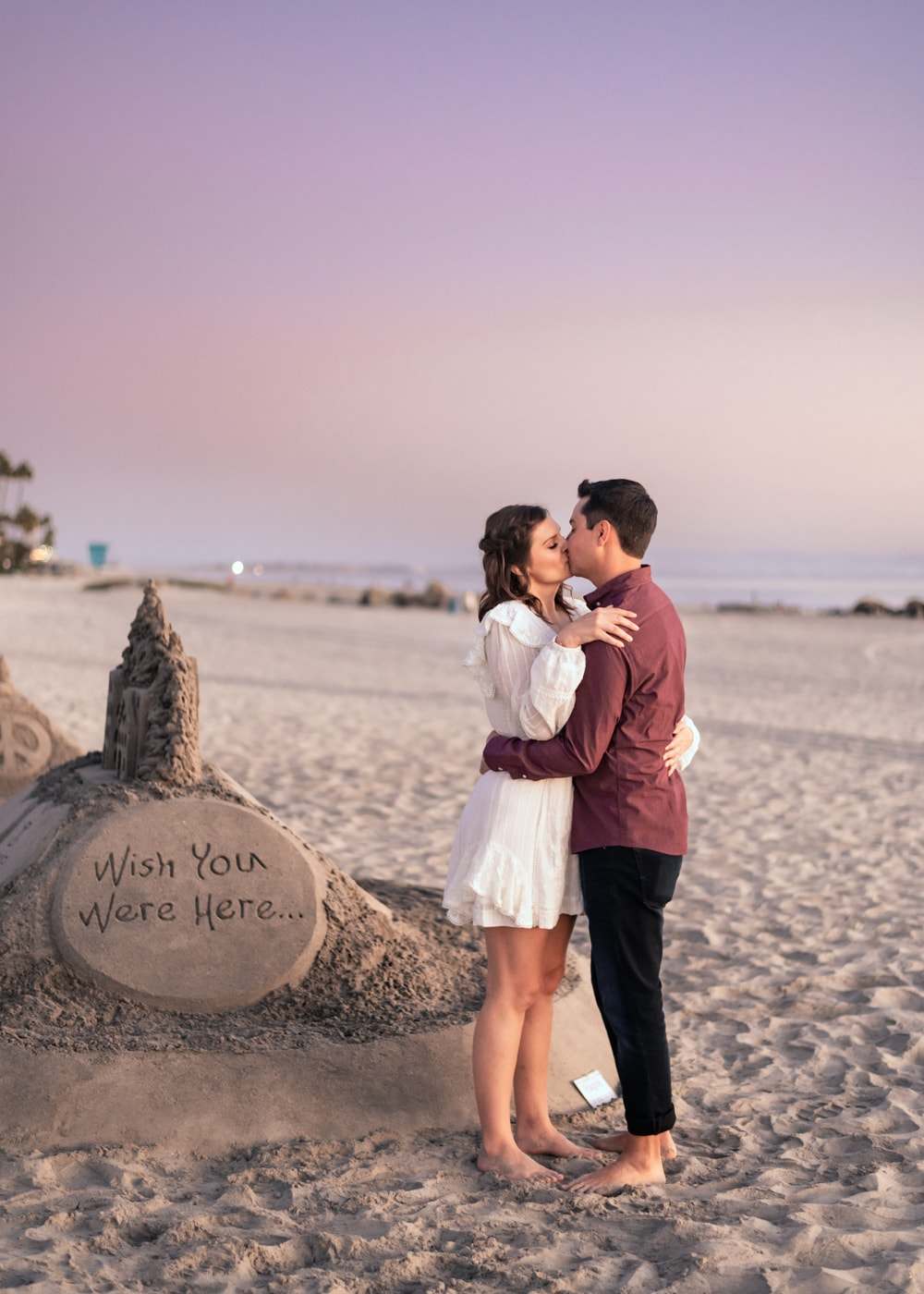 Couple kissing in front of sand sculpture at the Coronado sand dunes during their engagement session.
