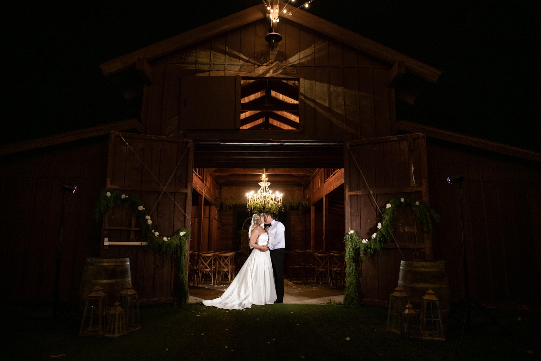 Bride and groom embracing in a barn at night at Ethereal Gardens.