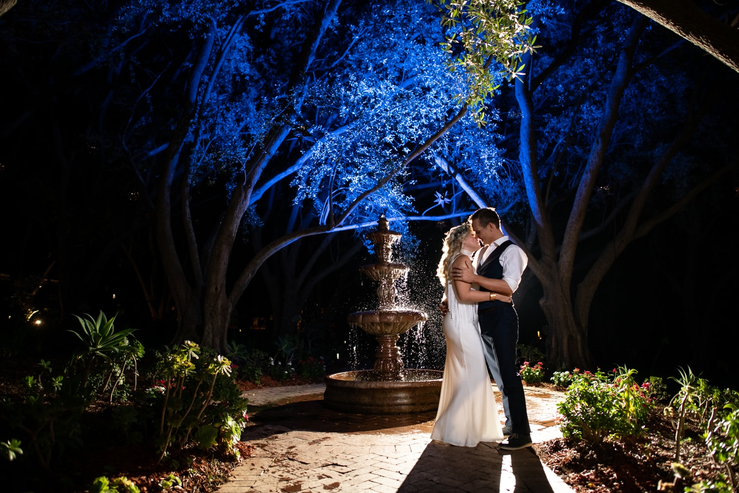 Bride and groom kissing by fountain at Padua Hills Theatre.