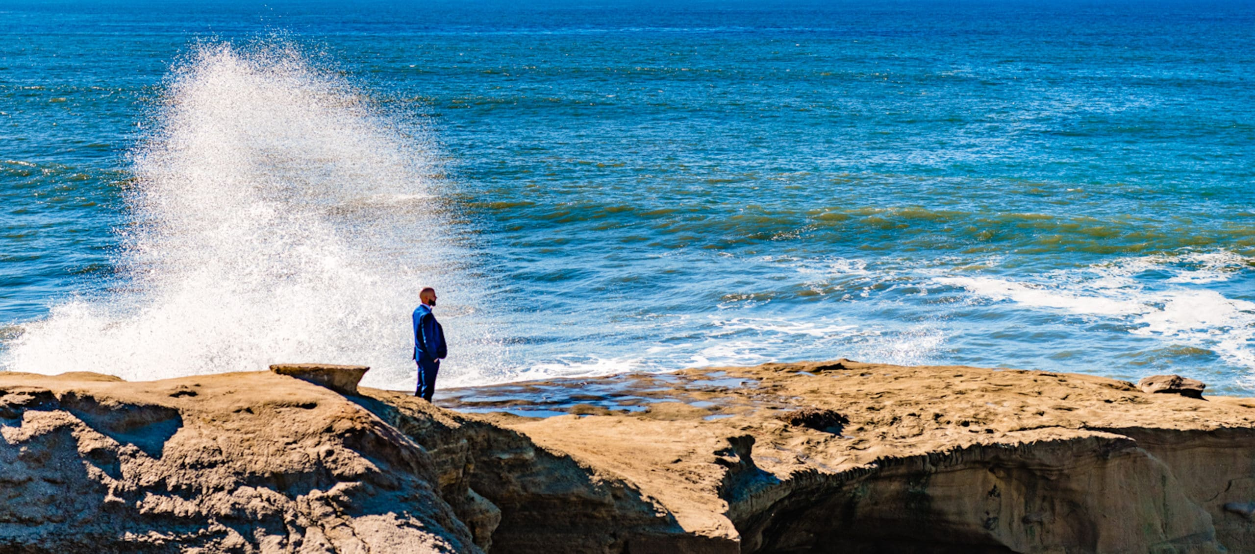 Groom awaiting first look with bride at sunset cliffs.
