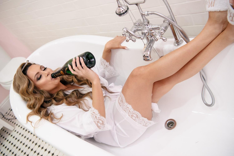 Bride sipping champagne in bathtub