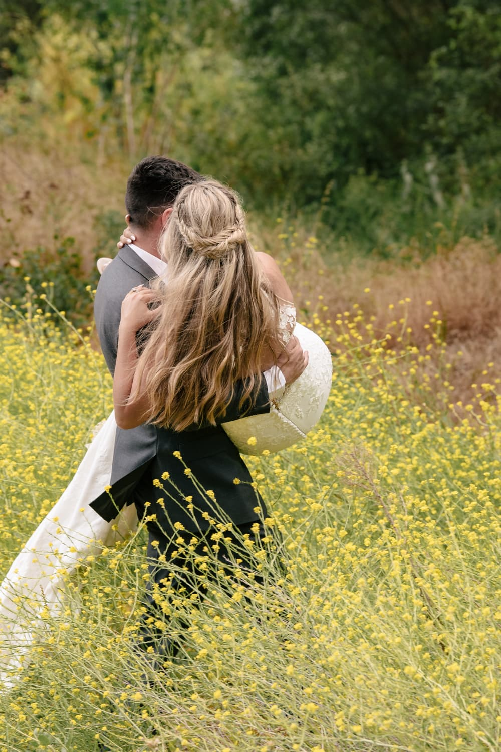 Groom carrying bride into wildflowers at The Stone House in Temecula, CA