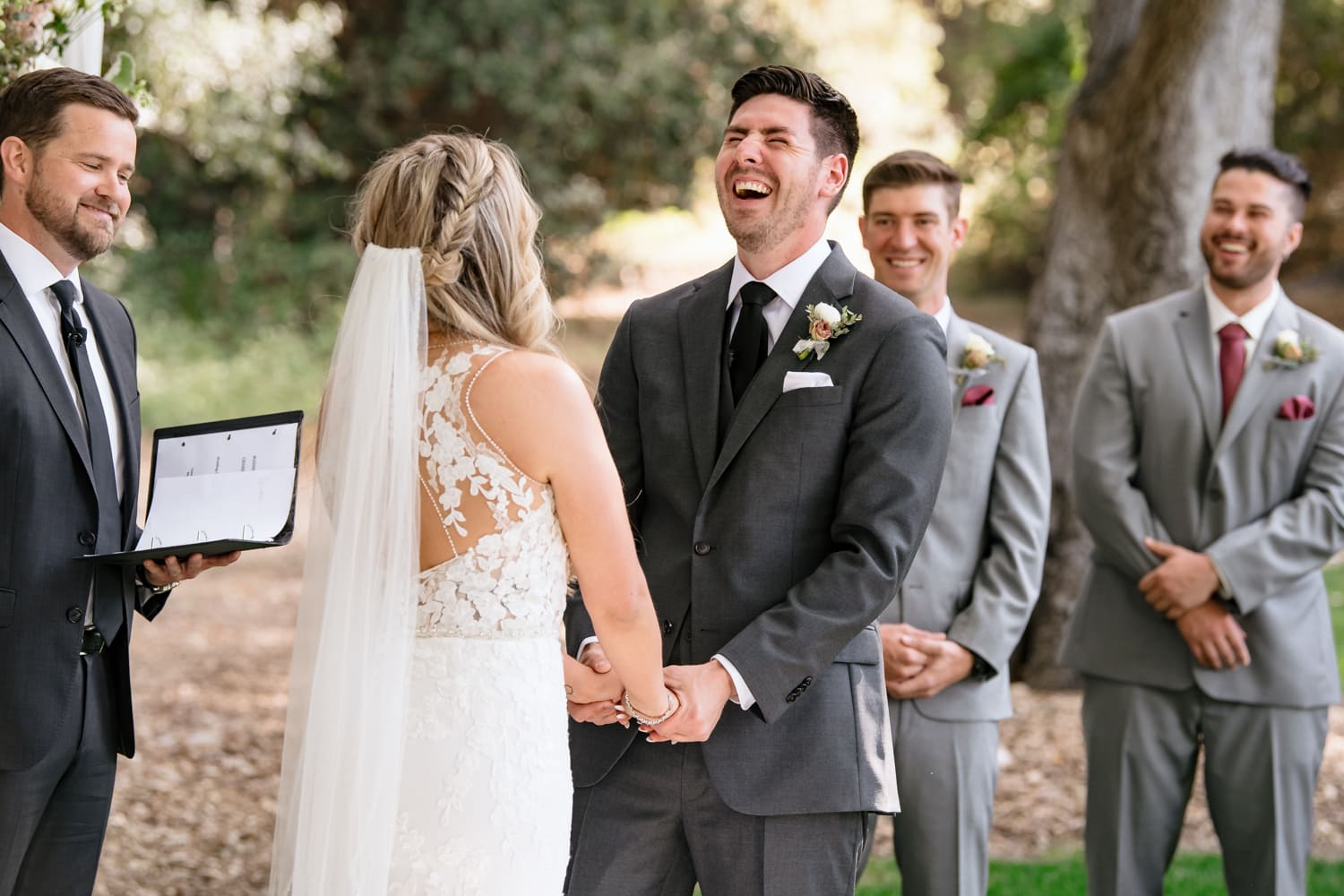 Groom laughing during Stone House wedding ceremony