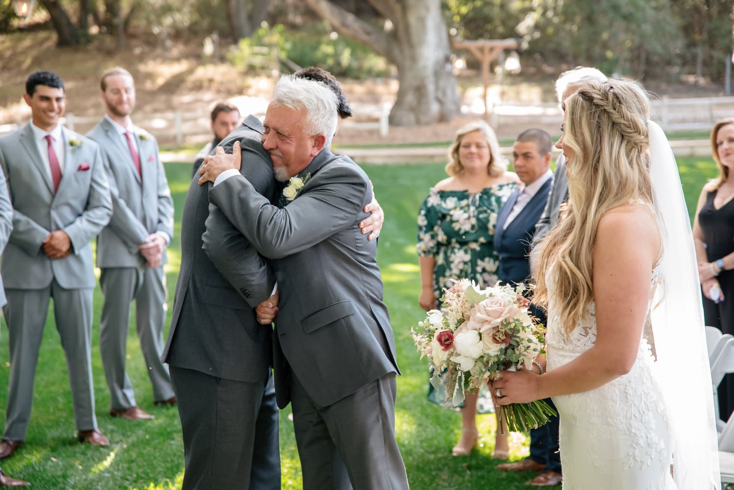 Father of bride hugging groom at Stone House Ceremony in Temecula, CA