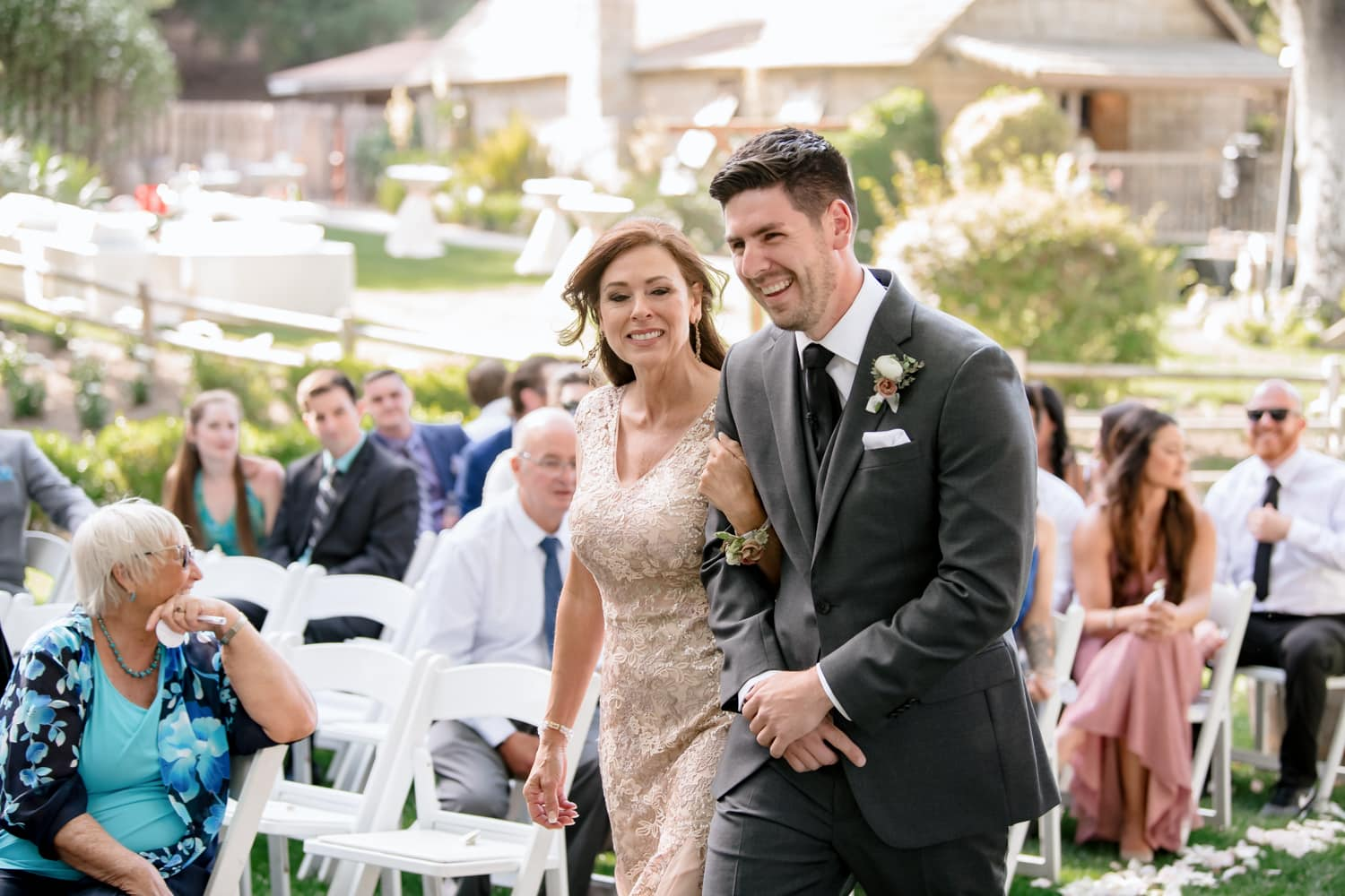Groom and mother walking into Stone House wedding ceremony